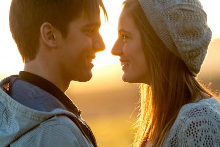 jovenes enamorados: Close up retrato de la joven pareja en la expresión de amor con la cara al atardecer.
