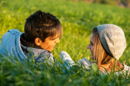 Close up portrait of handsome couple laying in grass field at sunset. Stock Photo - 16985364