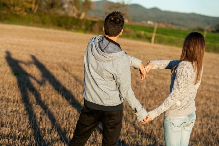 Young couple having fun creating love symbol outdoors. Stock Photo - 16985402