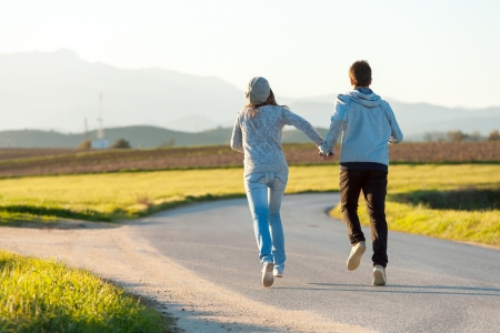 giving back: Young couple running along country road. Stock Photo