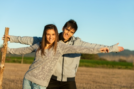 Portrait of cute couple stretching arms in countryside.