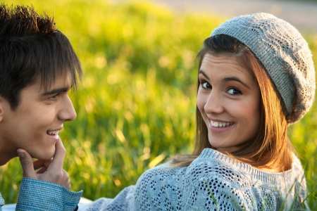Close up portrait of cute teen girl and boyfriend laying in green grass field. Stock Photo - 16985361