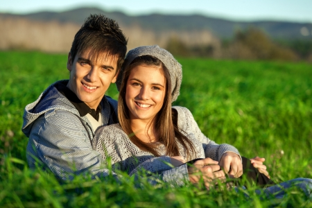 Close up portrait of handsome teen couple sitting in green grass field. Stock Photo - 16971370