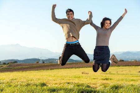 Young teen couple having fun jumping outsoors. photo