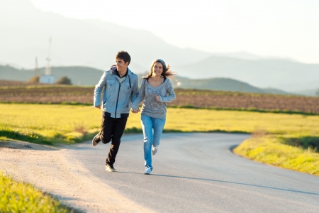 Teen couple running along road in countryside. Stock Photo - 17244813