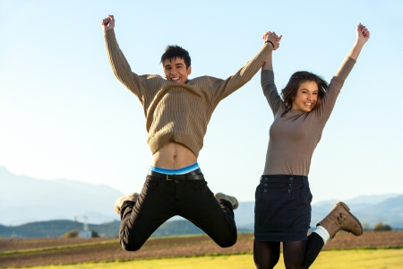 Young couple holding hands jumping outdoors. Stock Photo - 17244811