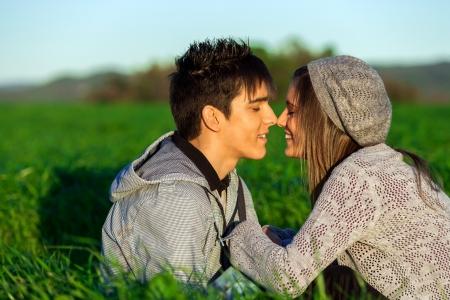 pareja de adolescentes: Primer plano retrato de una pareja joven y guapo en el campo mostrando afecto.