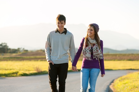 couple holding hands: Young couple wandering along road in countryside.