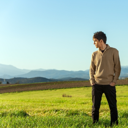 country boy: Portrait of young man standing in green field.