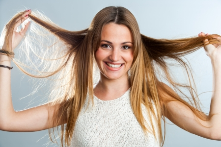 body care: Close up beauty portrait of girl playing with long hair. Stock Photo