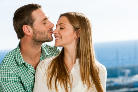Close up portrait of boyfriend kissing girl on nose outdoors. photo