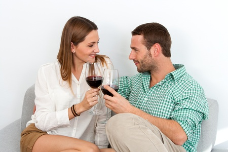 Close up portrait of couple enjoying a glass of red wine on couch indoors. Stock Photo - 17239244
