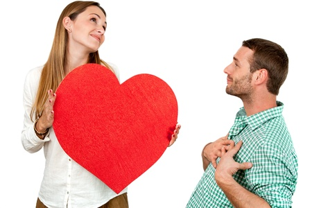 Close up portrait of couple playing around with big red heart symbol.Isolated on white background. photo