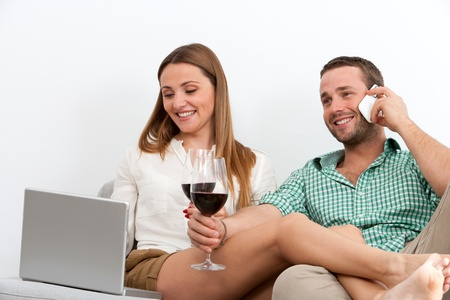 couple couch: Close up portrait of couple relaxing on couch with a glass of red wine.
