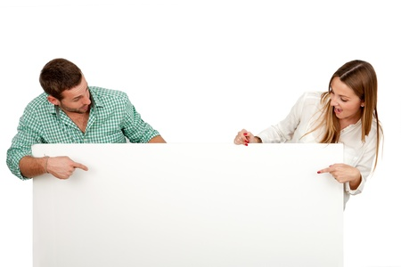 indicating: Couple with surprised look pointing on blank board.Isolated on white.