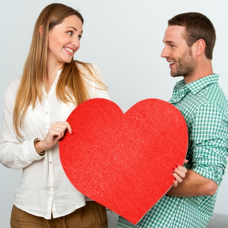 Close up portrait of cute couple holding big red heart symbol. Stock Photo - 17239246