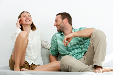 Portrait of handsome couple sharing laughs on couch. Stock Photo - 17239238