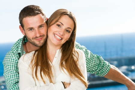 niñas sonriendo: Primer plano retrato de una pareja joven y atractiva en la playa.