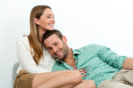Portrait of happy couple relaxing on couch indoors. photo