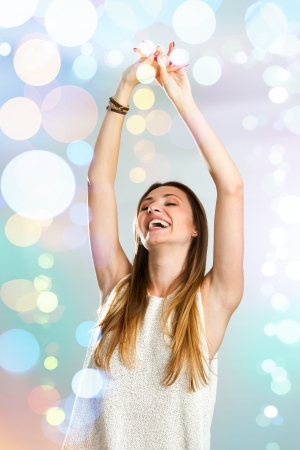 Attractive young woman dancing with festive color background. photo