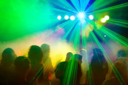 Festive atmosphere of people dancing under disco laser beam.