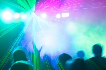 nightclub crowd: Colorful disco laser lights illuminating crowd at party. Stock Photo