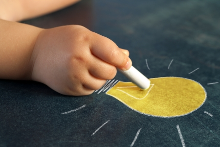 Macro close up of infant hand drawing a yellow bulb on blackboard. Stock Photo