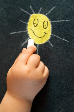 infant hand: Macro close up of infant hand drawing a smiling yellow sun on blackboard.