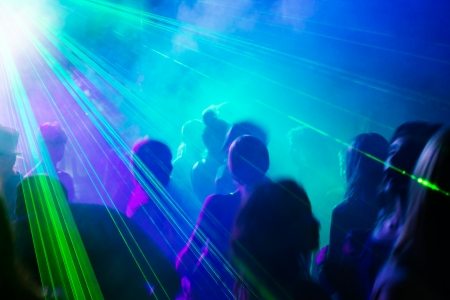 party silhouettes: Crowd of people dancing under disco laser light.