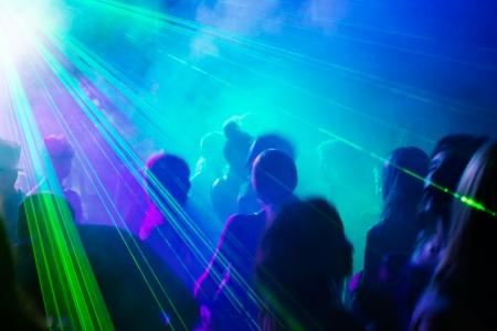 gente loca: Multitud de gente bailando bajo la luz l�ser discoteca.