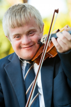Close up portrait of young handicapped violinist outdoors. photo