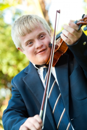 disadvantaged: Portrait of cute boy with down syndrome playing violin outdoors. Stock Photo