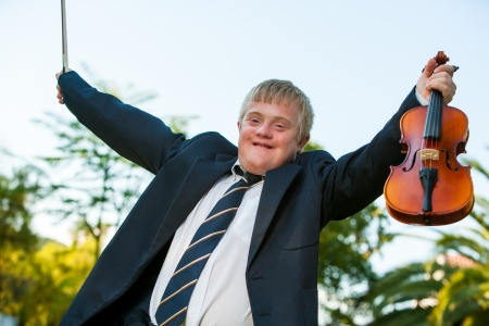 down syndrome: Happy handicapped violinist raising arms outdoors. Stock Photo