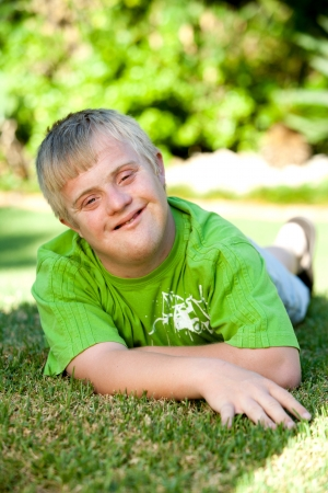 Portrait of cute handicapped boy laying on green grass. Stock Photo