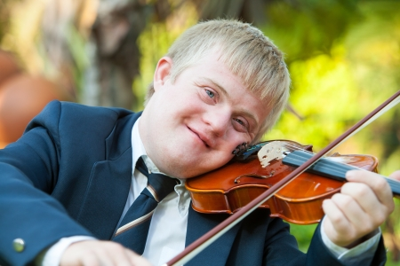 syndrome: Portrait of young handicapped violinist practicing outdoors.