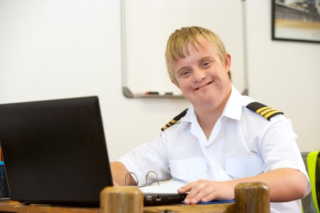 syndrome: Portrait of young handicapped pilot working at desk.