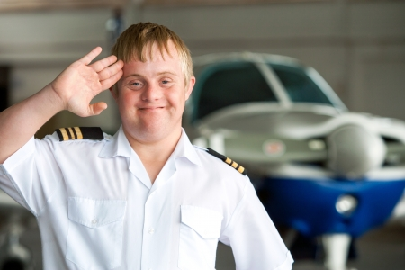 down: Portrait of young pilot with down syndrome saluting in hangar.