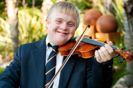 Close up portrait of friendly handicapped boy playing violin outdoors. photo