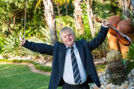 wind down: Young handicapped musician raising arms with violin outdoors.