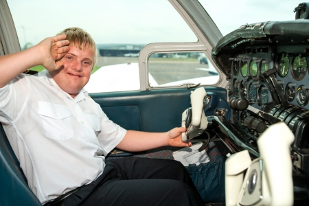 challenged: Portrait of young handicapped pilot saluting before takeoff.