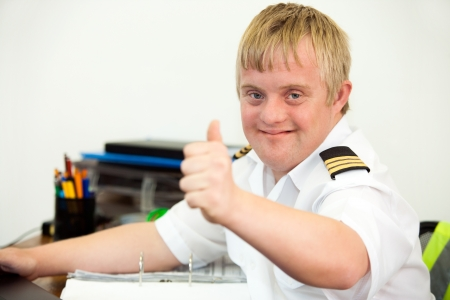 handicap people: Portrait of young handicapped pilot showing thumbs up at office desk.
