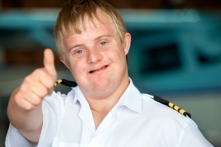 face down: Portrait of young pilot with down syndrome showing thumbs up.