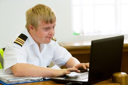 handicap: Giovane pilota con sindrome di Down che lavora con i computer scrivania.