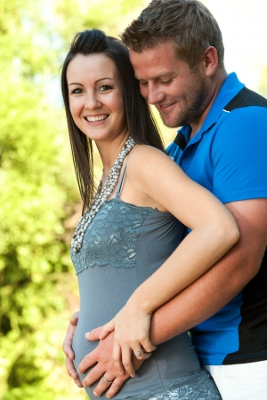 Close up portrait of young husband touching wifes pregnant tummy outdoors. photo