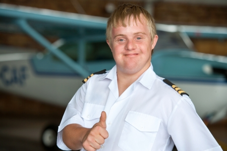 syndrome: Portrait of young handicapped pilot showing thumbs up in hangar.