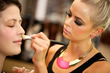 maquillage: Close up portrait of cute blond make up artist applying color on face. Stock Photo