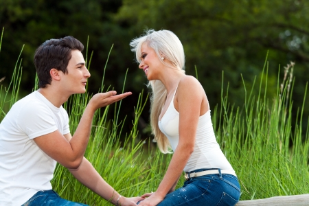 blonde close up: Close up portrait of handsome young man blowing a kiss to girl outdoors. Stock Photo