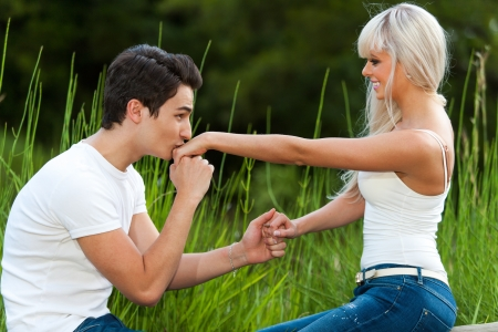 women kissing women: Portrait of young man proposing to girl with kiss on the hand.