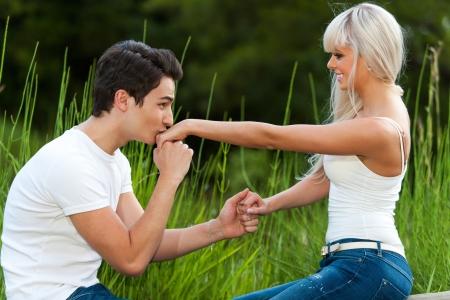enamorados besandose: Retrato de hombre joven propone a la muchacha con beso en la mano. Foto de archivo