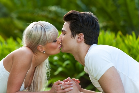 Close up portrait of young couple kissing in park. photo